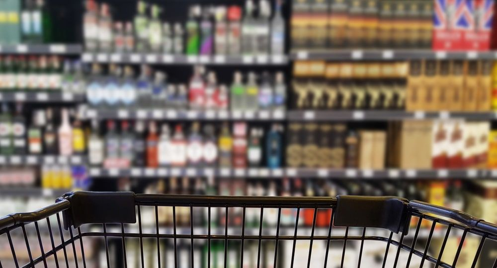 Abstract blurred image of alcohol store with trolley (Selective