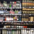 Abstract blurred image of alcohol store with trolley (Selective focused at shopping cart)