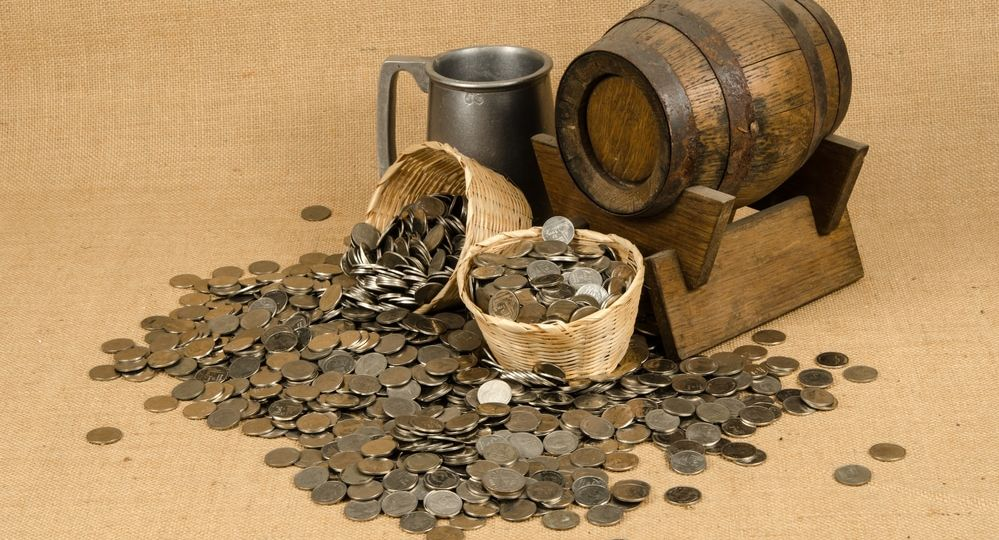 Stack of coins with wooden barrel