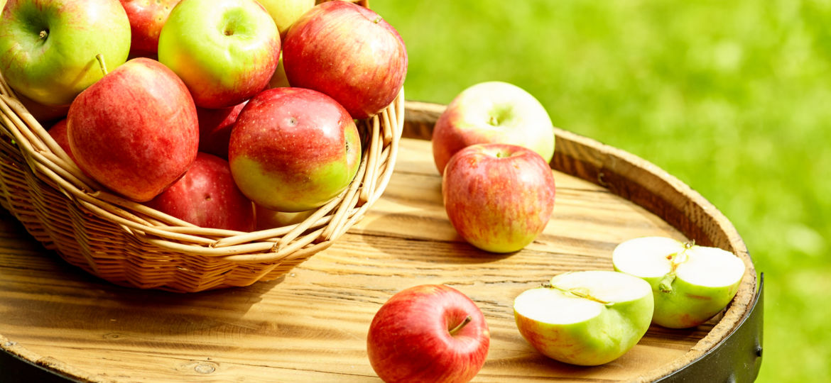 Beautiful apples on garden background on the old barrel