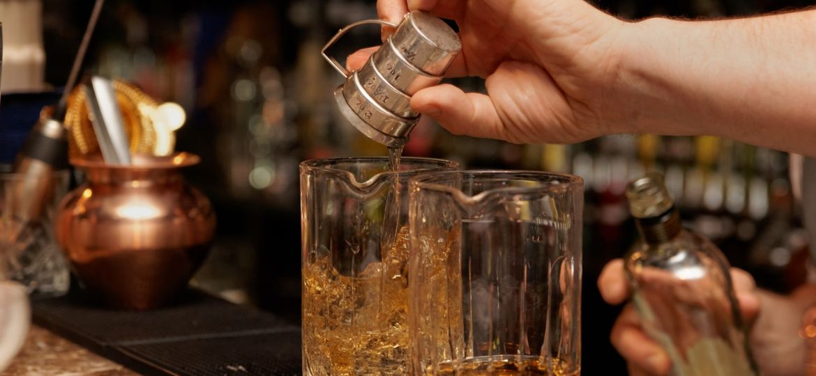 Bartender is pouring whisky in glass