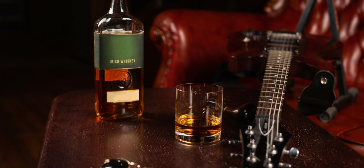 A bottle of Irish whiskey, with a glass, glasses, and a guitar o