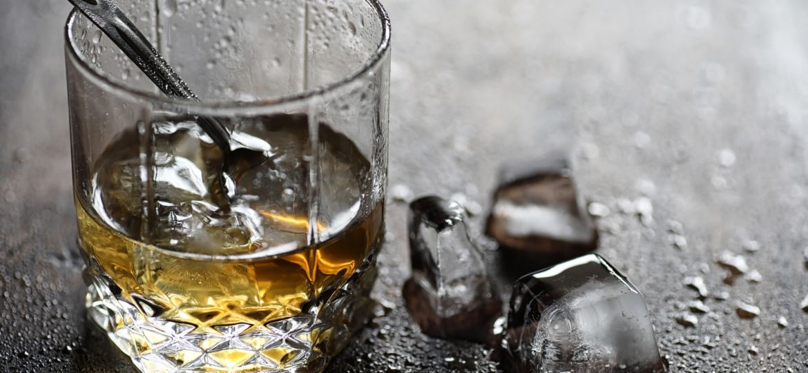 Whiskey in a glass and pieces of ice on a wood