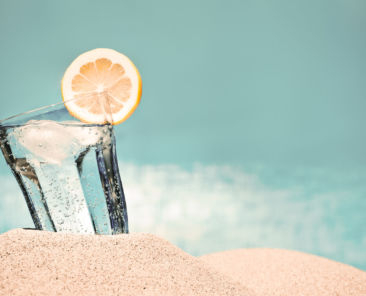 Cold drink with ice and a slice of lemon on the beach on a hot summer day