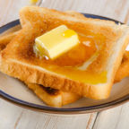 Slices toast bread with butter on a wooden background .