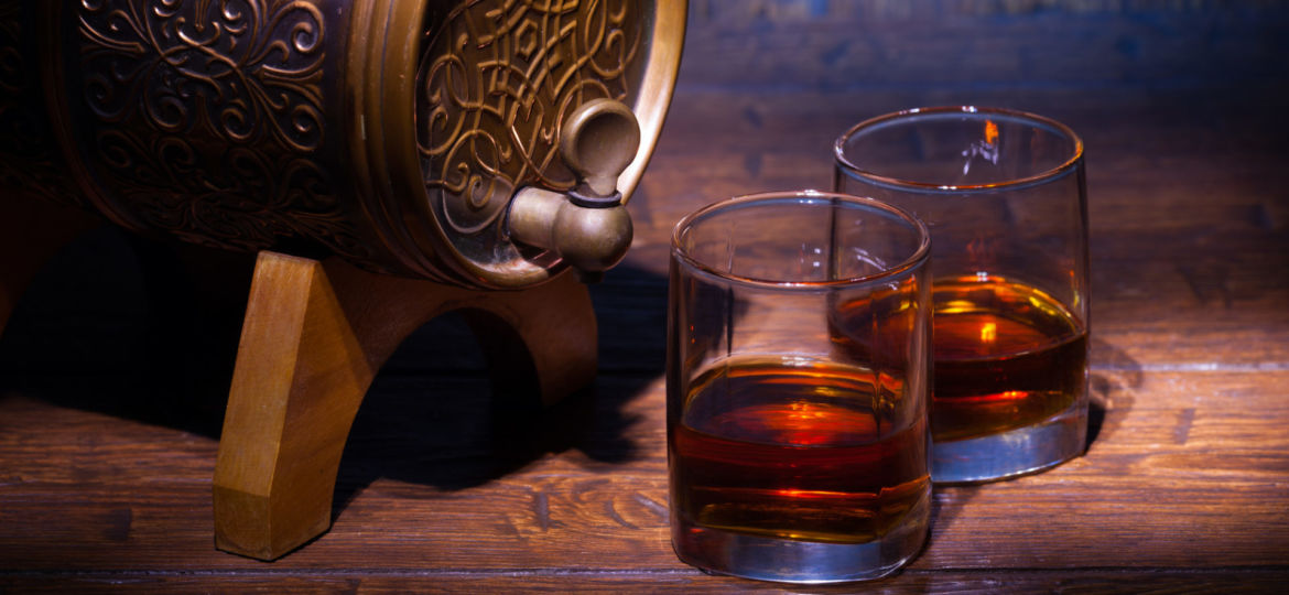 Glasses of whiskey and small barrel on wooden table