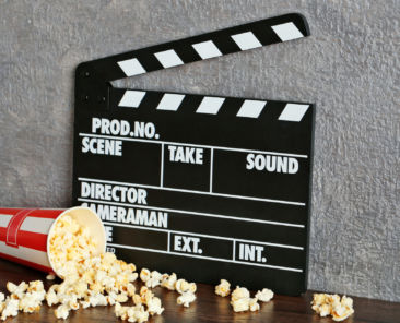 Movie clapper and popcorn against grey wall background